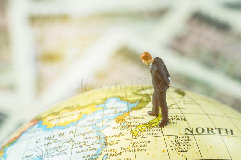 Miniature figure country leader man standing and looking at north korea map on globe as world critical nuclear missile war. Situation or war talk negotiation stock images