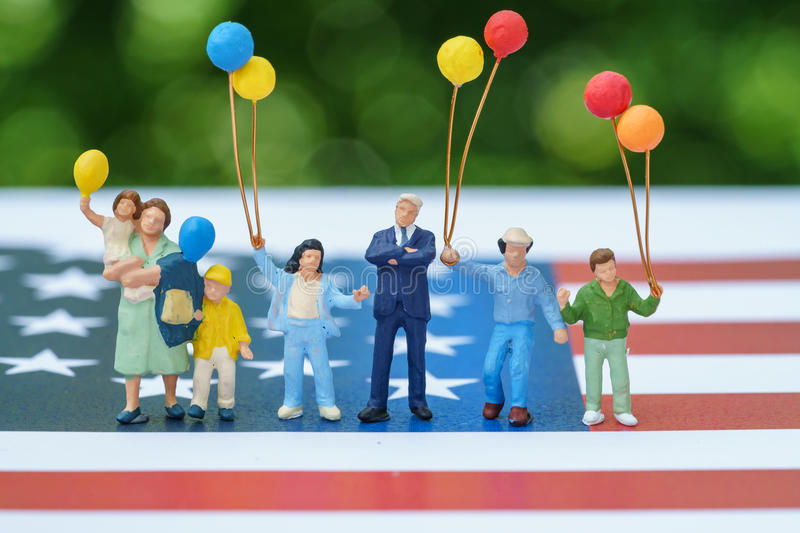 Miniature figure, happy american family holding balloon with Uni. Ted State national flag in green bokeh background as celebrating the Independence day stock photos