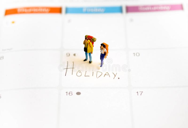 Miniature figure : Man and women are standing on the calendar in the holiday`s date and holding the backpack for travelling stock photography