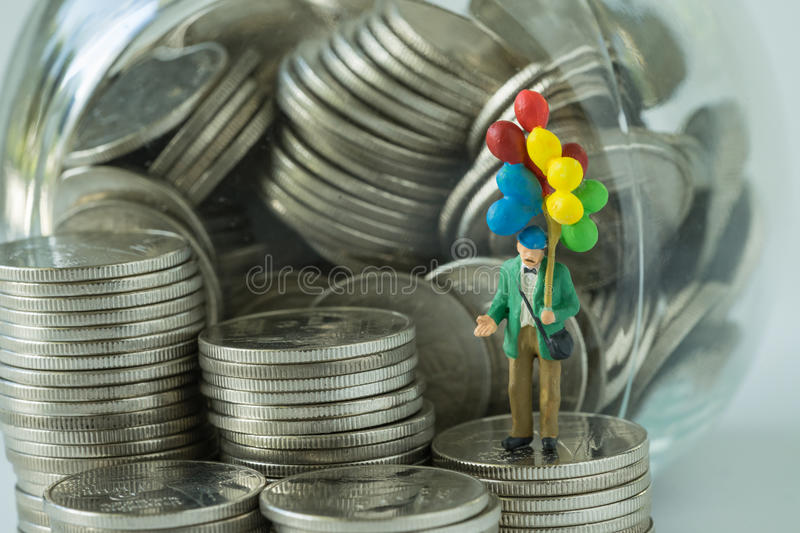 Miniature figure old man holding balloon standing on coins, money in the jar as happy retirement saving concept stock images