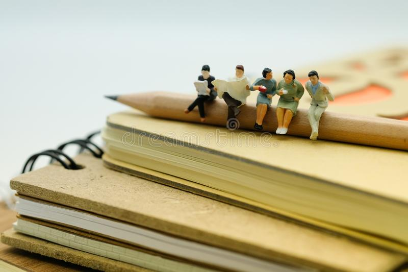 Miniature Figure : People sitting on the stack of notebook. They stock images
