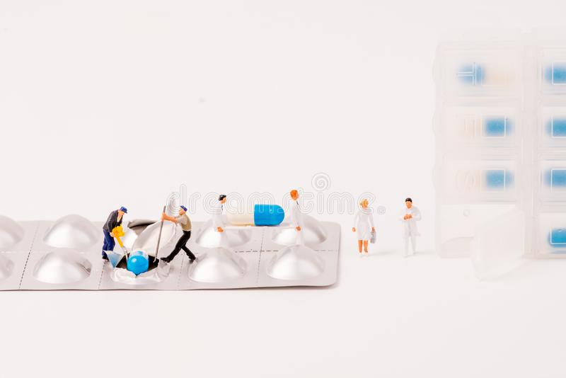 Miniature figure people working with drug daily container. On white background,medical concept royalty free stock image