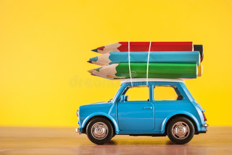 Miniature figure toy car Mini Morris carrying colored pencils on roof on yellow royalty free stock photo