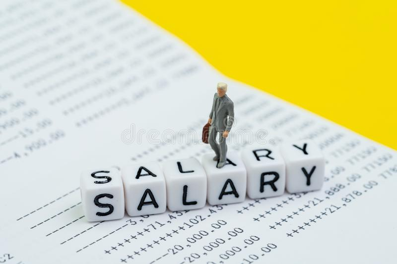 Miniature figure working businessman, office guy walking on cube block building word Salary on bank deposit account book on yellow. Background, Salary man stock photo