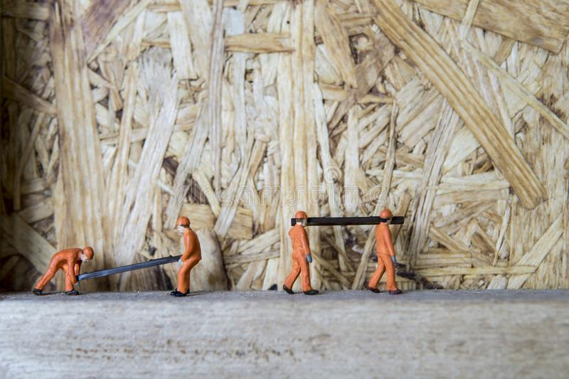 Conceptual miniature. Miniature figure working in industrial - Close up of construction workers teamwork concept with selective focus royalty free stock images
