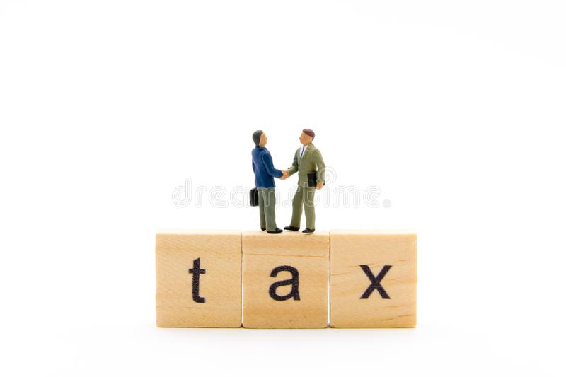 Miniature figures as business men standing over wooden blocks with letters making Tax word and shaking hands, isolated on white royalty free stock images