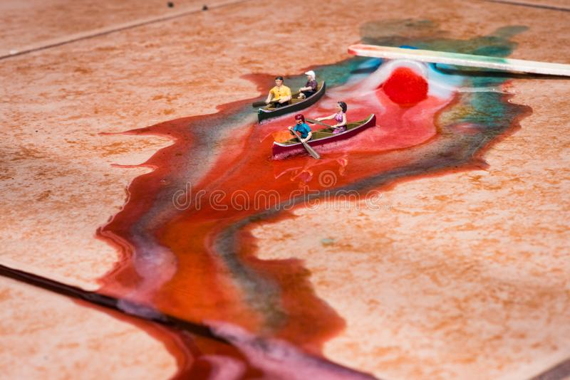 Miniature Figures Canoeing on a Melted Popsicle stock photography