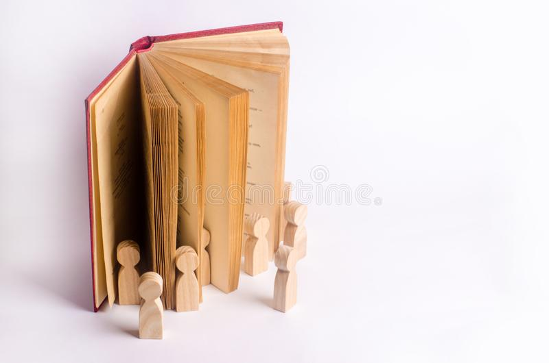 Miniature figures of people come out of the book into the real world. The book comes alive royalty free stock images
