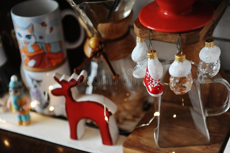 Miniature figures of skates and mittens as Christmas decorations in focus. Coffee accessories on blurred background stock photography