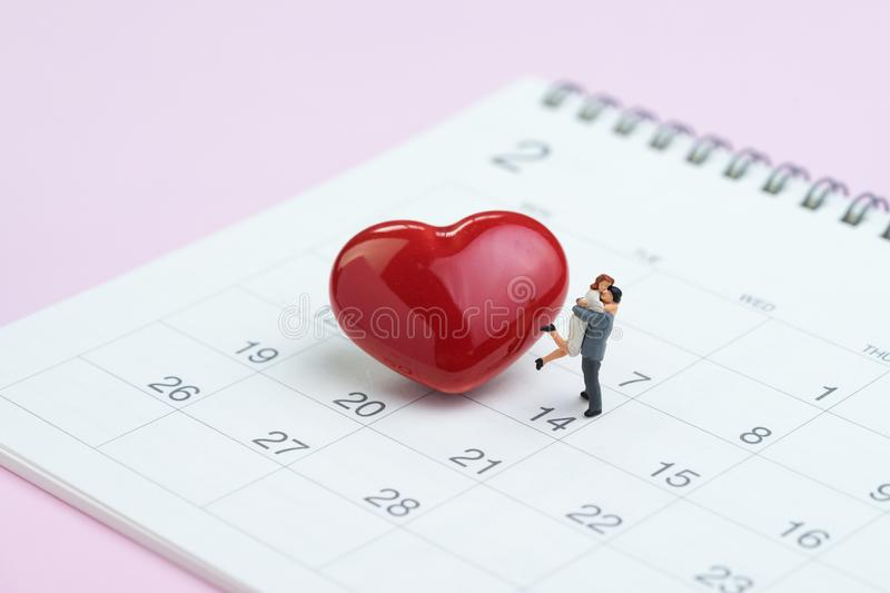 Miniature figures sweet couple standing with shiny red heart sha stock photography