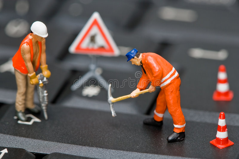 Miniature figures working on a computer keyboard. royalty free stock image