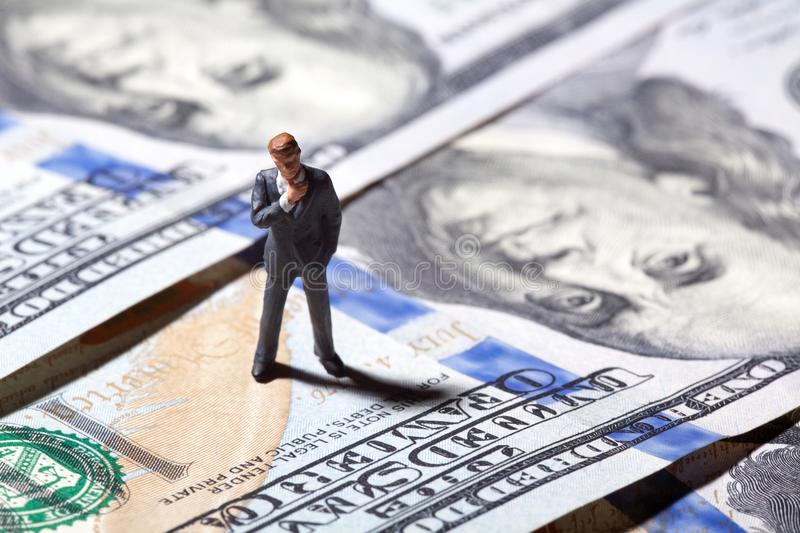 Miniature figurine businessman with 100 dollars banknote on background stock photography