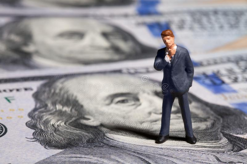 Miniature figurine businessman with 100 dollars banknote on background royalty free stock image