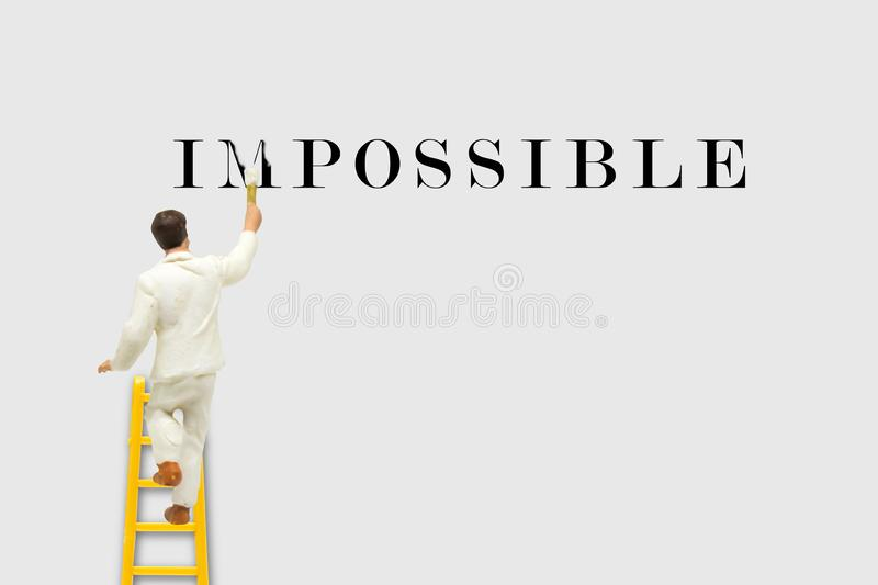 Miniature figurine character as painter standing on wooden ladder and painting to change the word Impossible to Possible. stock photography