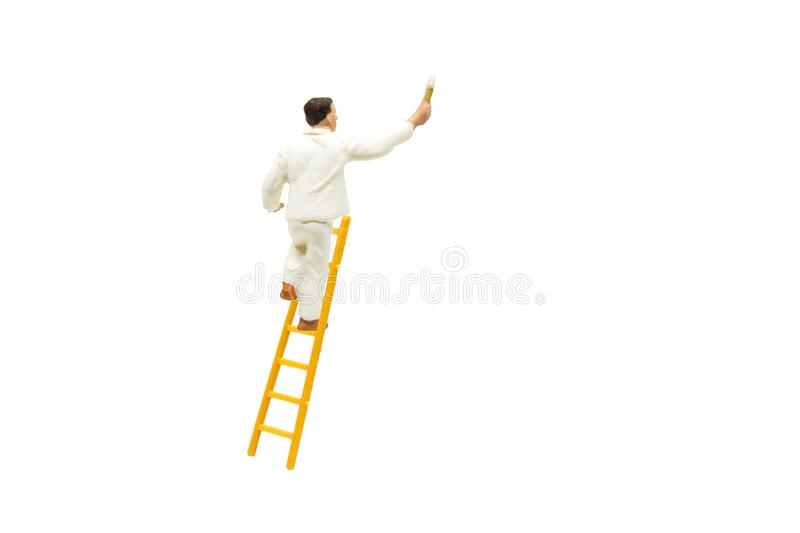 Painter standing on wooden ladder and painting wall with paint tools isolated on white background. stock photography