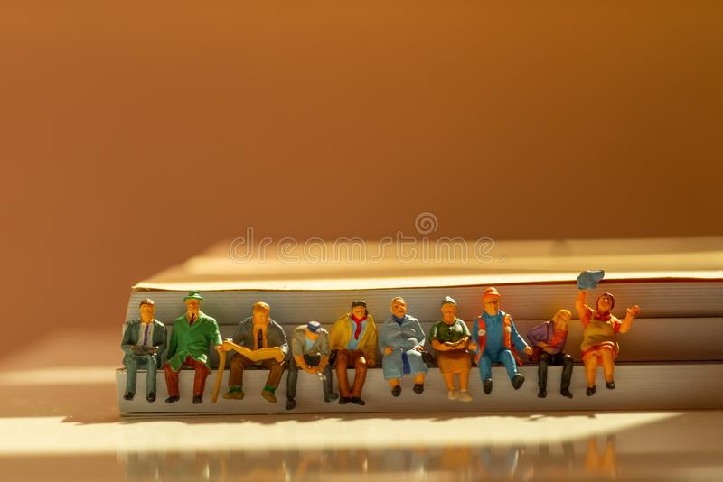 Miniature figurines of various types people sitting in a row concept royalty free stock images