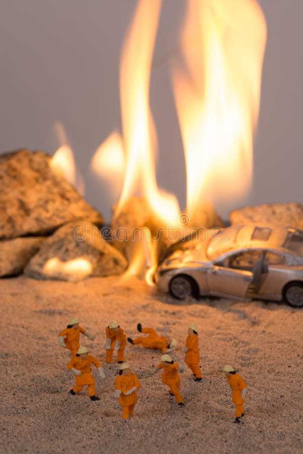 Miniature firemen at a car accident scene in flames. Close up stock images