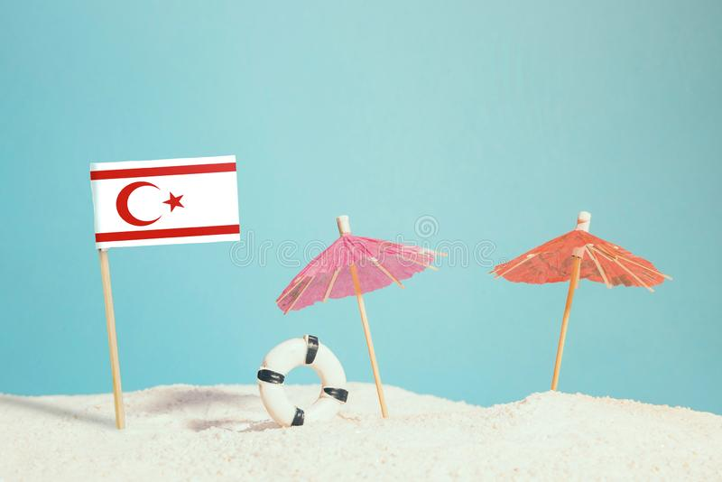 Miniature flag of Northern Cyprus on beach with colorful umbrellas and life preserver. Travel concept, summer theme royalty free stock images