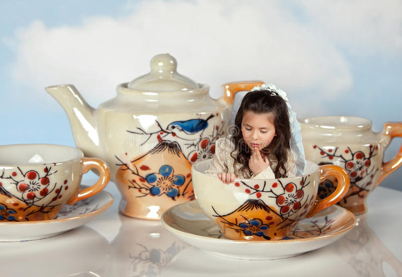 Miniature girl on tea party. Tea party with antique tea cups and a miniature girl like in alice in wonderland royalty free stock image