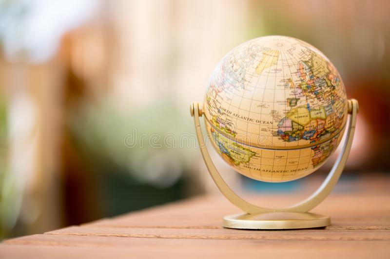 Miniature globe model on a rustic wooden table. Symbol for travelling royalty free stock photo