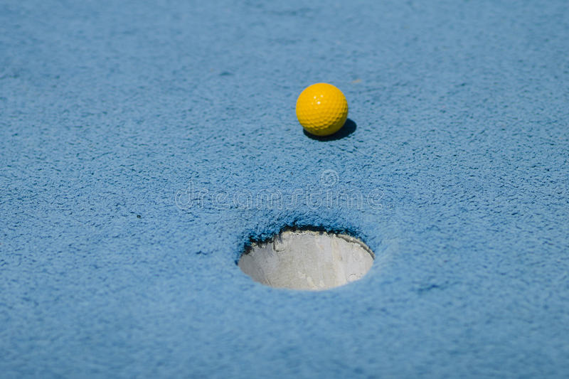 Miniature Golf Ball Approaching Hole Close-Up royalty free stock images