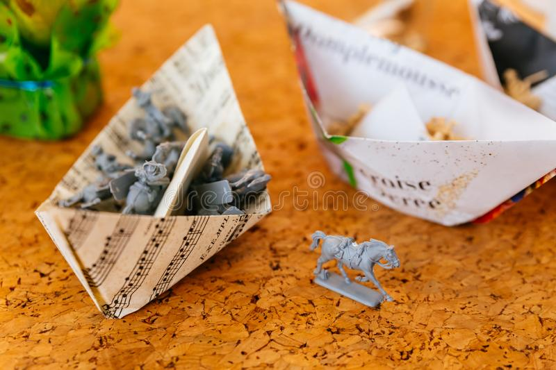 Miniature gray horse with miniature models in paper folding boats stock images