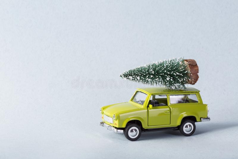 Miniature green car with x-mas tree on is top stock image