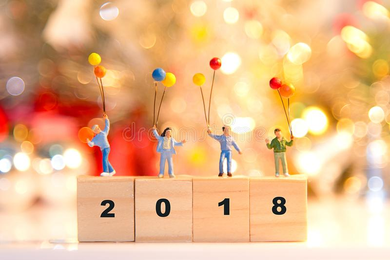 Miniature group happy family holding balloons standing on wooden 2018 with party happy new year, stock photos