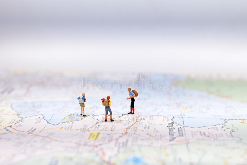 Miniature Group traveler with backpack standing on wold map for travel around the world. Travel Concept, stock photography