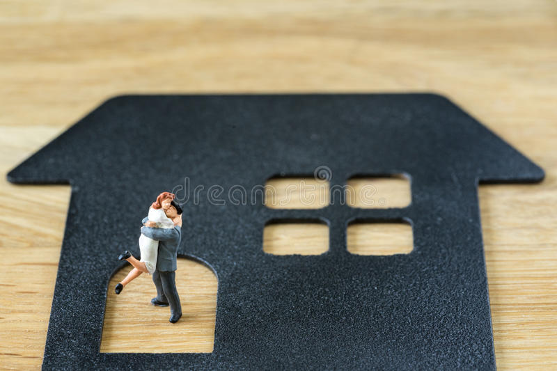 Miniature happy couple family figure standing on paper house wit royalty free stock photos