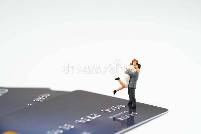 Miniature happy couple holding each other standing on pile of credit card on white background with copy space, success family. Financial management or online royalty free stock photo