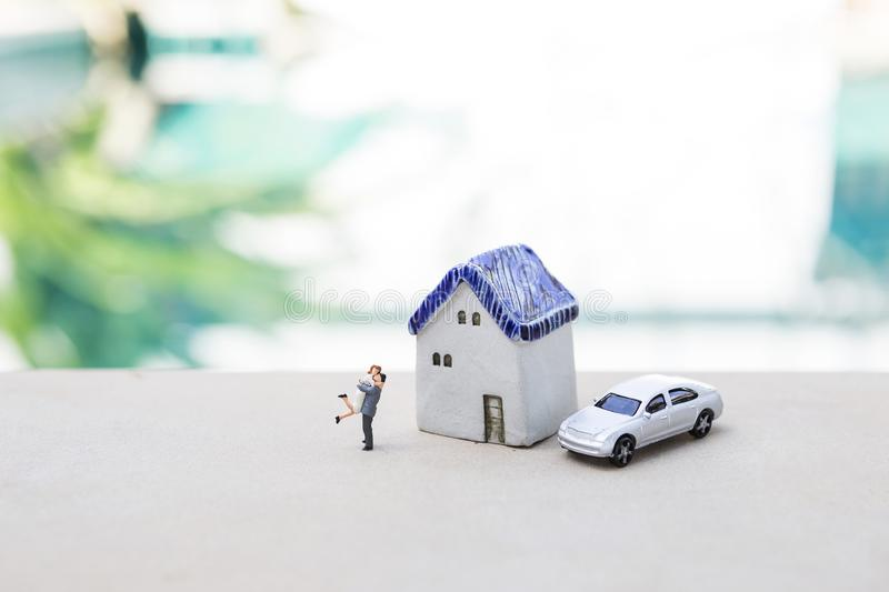 Miniature happy couple with miniature house and model car over blurred swimming pool background royalty free stock photography
