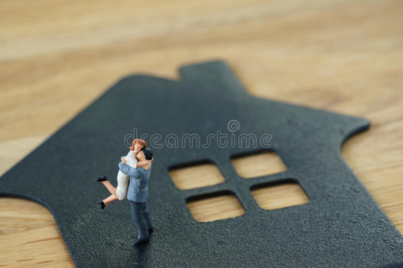 Miniature happy family figure standing on paper house as property or financial investment mortgage plan concept royalty free stock photo