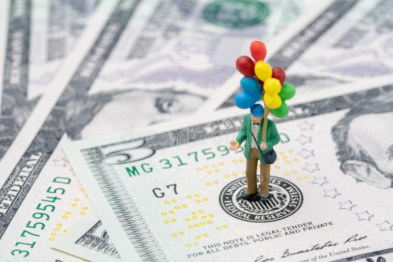 Miniature happy man holding colorful balloons on US Federal Reserve emblem on US dollars banknote as FED consider interest rate royalty free stock image