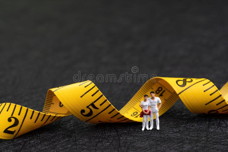 Miniature healthy people figure in white, man and woman young fitness family standing with yellow measuring tape using as fitness stock images