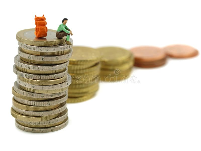 Miniature hiker sits on stack of euro coins, concept of financial independence, a long way to success royalty free stock photography