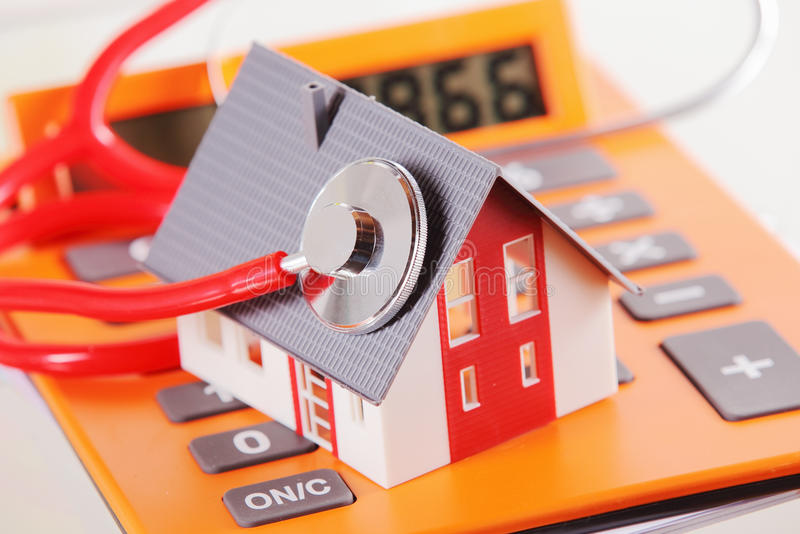 Miniature Home with Stethoscope on a Calculator stock photo