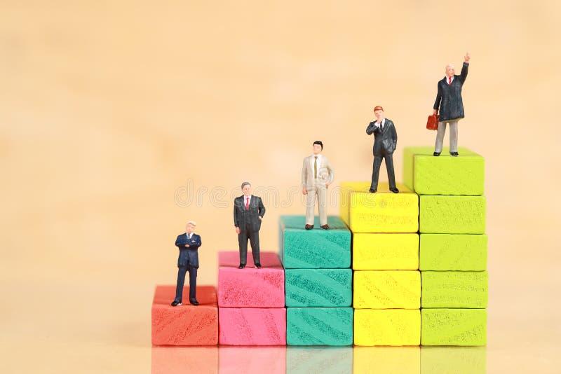 Miniature : homme d'affaires debout sur un podium en bois en arrière-plan Concept de concurrence financière et commerciale photographie stock