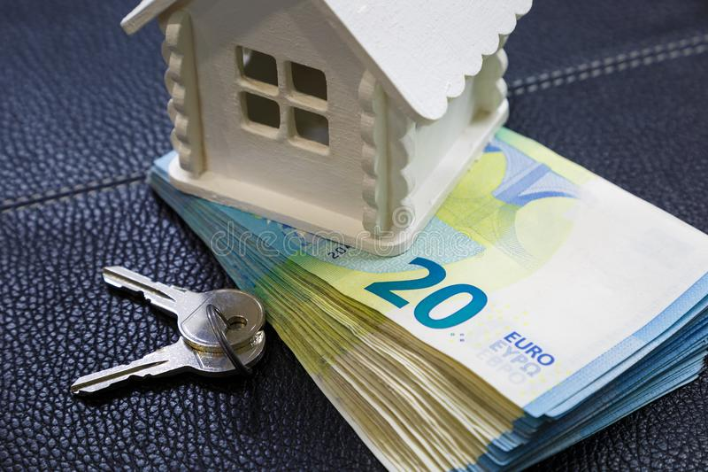 Miniature house, a bundle of money and keys lie on the black leather surface stock image