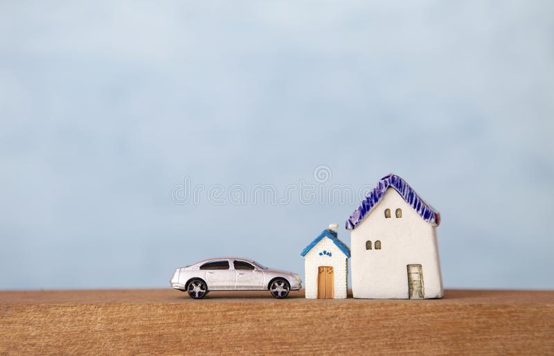 Miniature house and car on wooden floor over blurred blue background stock photo