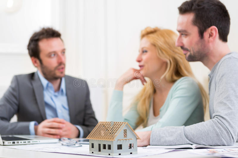Miniature house in a desk of real estate agent with couple royalty free stock photos