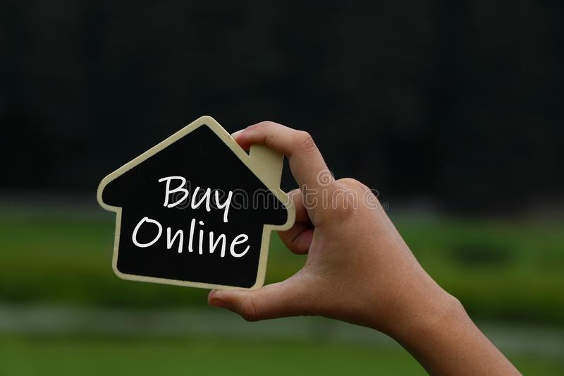 Miniature house in hands with text buy online on it. Property investment, house mortgage and saving money financial concept royalty free stock photo