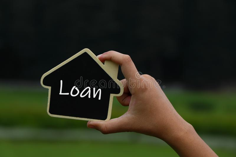 Miniature house in hands with text loan on it. royalty free stock image