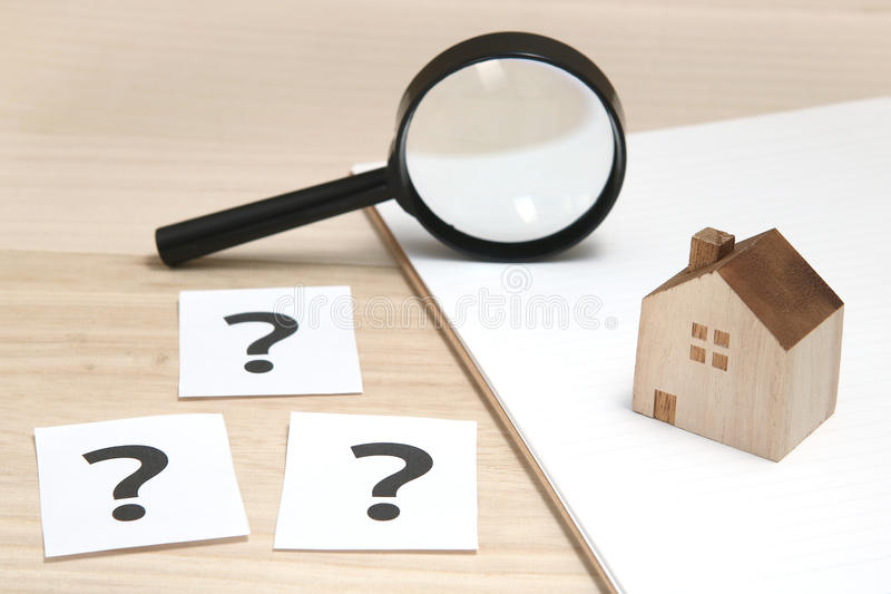 Miniature house and many question marks on white papers. House with question marks and magnifying glass. Real Estate Concept. royalty free stock image