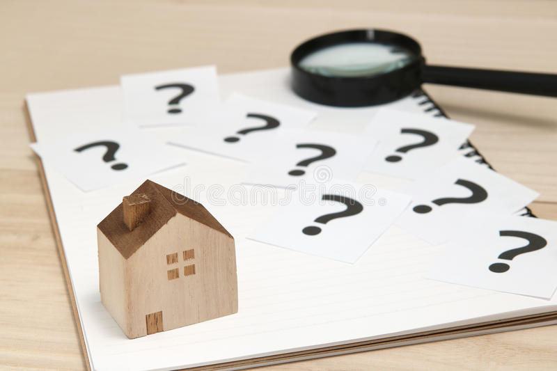Miniature house and many question marks on white papers. House with question marks and magnifying glass. Real Estate Concept. stock photography