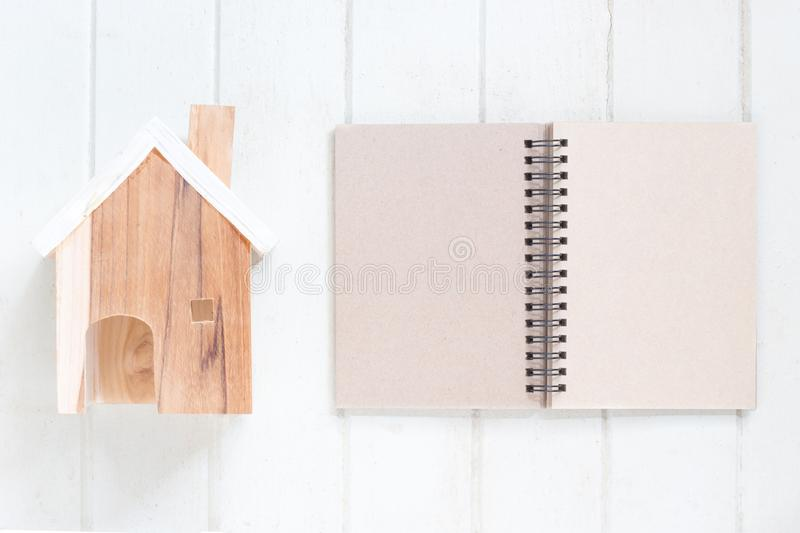 Miniature house model with blank paper notebook. On white wood background, copy space stock photography