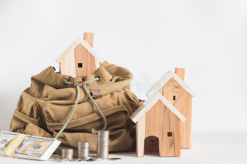 Miniature house model in the brown color Backpack and beside have dollar bills, money coins on white background royalty free stock photo