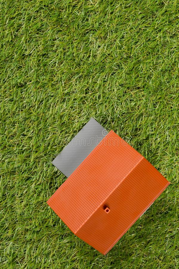 Miniature house model on green grass lawn background top view flat lay from above - house building or buying concept royalty free stock photo
