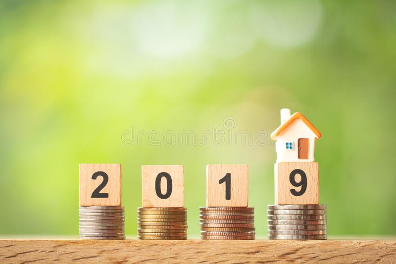 Miniature house model on year 2019 on coin stacks on greenery blurred background royalty free stock photography
