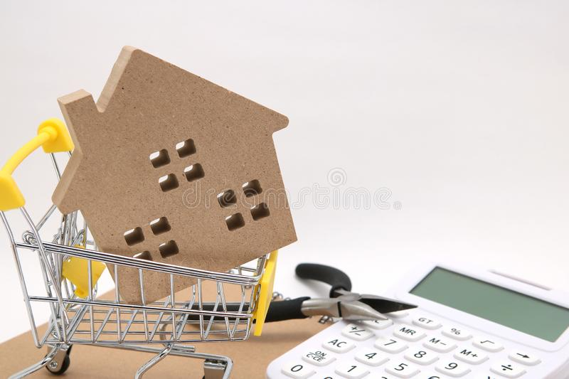 Miniature house, shopping cart, calculator and tools on white background. Concept of buying new house, real estate and renovation. royalty free stock photos